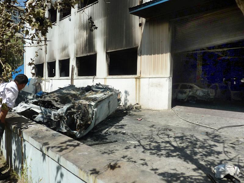 In this Sept. 16, 2012 photo, a man looks at a burnt car after anti-Japan demonstrators attacked a Japanese auto dealership and burned vehicles in Qingdao in Sandong Province, China. Sales of Toyota and Honda vehicles nosedived in China during September as anti-Japanese sentiment flared over a territorial dispute that threatens to hobble what was a booming business relationship between Japan and its biggest export market. Toyota Motor Corp. said Tuesday, Oct. 9, that sales of new vehicles in China dropped 48.9 percent in September from a year earlier to 44,100 vehicles. Honda Motor Co. said September sales plunged 40.5 percent to 33,931 vehicles. China sales for Nissan Motor Co. slid 35.3 percent last month to 76,100 vehicles. (AP Photo/Kyodo News) JAPAN OUT, MANDATORY CREDIT, NO LICENSING IN CHINA, FRANCE, HONG KONG, JAPAN AND SOUTH KOREA