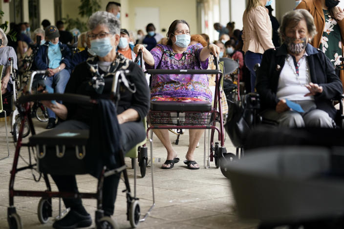 FILE - In this Jan. 12, 2021, file photo Resident Sabeth Ramirez, 80, center, waits in line with others for the Pfizer-BioNTech COVID-19 vaccine at the The Palace assisted living facility in Coral Gables, Fla. An ongoing study suggests that older American adults are showing resilience and perseverance despite struggles with loneliness and isolation during the pandemic. (AP Photo/Lynne Sladky, File)