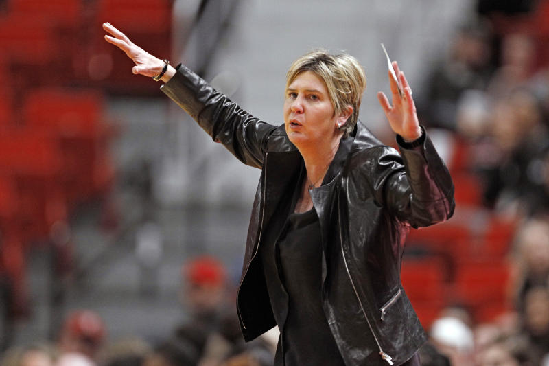 Marlene Stollings in a black jacket, hands raised.
