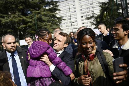 Emmanuel Macron (C), head of the political movement En Marche !, or Onwards !, and candidate for the 2017 presidential election, holds a girl during a campaign visit in Sarcelles, near Paris, April 27, 2017.  REUTERS/Martin Bureau