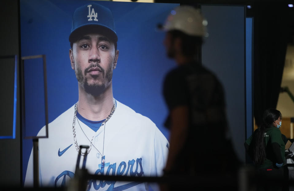 An image of Los Angeles Dodgers outfielder Mookie Betts stands behind workers during a media tour at the Play Ball Park exhibit at the Colorado Convention Center staged by Major League Baseball as part of the festivities leading up to the All Star Game Thursday, July 8, 2021, in Denver. The convention center has been turned into a paradise for baseball aficionados complete with batting cages, an onsite home run derby, items from the Hall of Fame and countless merchandise for sale for baseball fans from far and near at the store. (AP Photo/David Zalubowski)