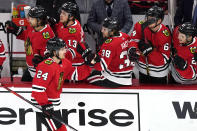 Chicago Blackhawks center Pius Suter (24) celebrates with teammates after scoring his first goal against the Detroit Red Wings Chicago Blackhawks during the first period of an NHL hockey game in Chicago, Sunday, Jan. 24, 2021. (AP Photo/Nam Y. Huh)
