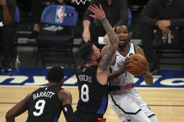 Brooklyn Nets forward Kevin Durant (7) drives to the basket against New York Knicks guards Austin Rivers (8) and RJ Barrett (9) during the first quarter of an NBA basketball game Wednesday, Jan. 13, 2021, in New York. (Brad Penner/Pool Photo via AP)