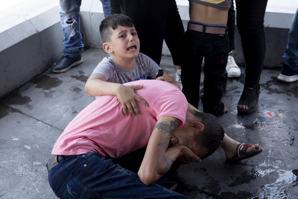 FILE - In this May 20, 2021, file photo, a boy screams for help after his father was injured when he was hit in the eye by a stone thrown by members of the Christian rightwing Lebanese Forces group, who attacked buses carrying Syrian voters, in the town of Zouk Mosbeh, north of Beirut, Lebanon. Mobs of angry Lebanese men attacked buses and cars carrying Syrians expatriates and others heading to the Syrian embassy in Beirut protesting against what they said was an organized vote for President Bashar Assad. (AP Photo/Hassan Ammar)