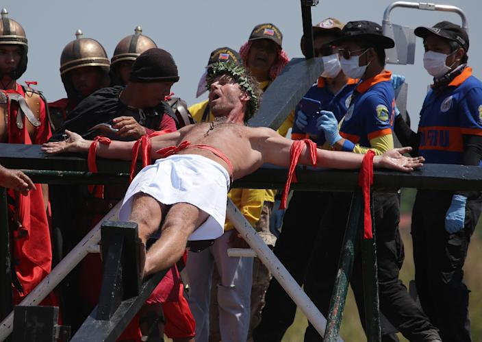 Danish national Lasse Spang Olsen, a 48-year-old filmmaker, grimaces as he is nailed to a cross to re-enact the crucifixion of Jesus Christ in San Juan village, Pampanga province, northern Philippines on Friday, April 18, 2014. Church leaders and health officials have spoken against the practice which mixes Roman Catholic devotion with folk belief, but the annual rites continue to draw participants and huge crowds. (AP Photo/Aaron Favila)