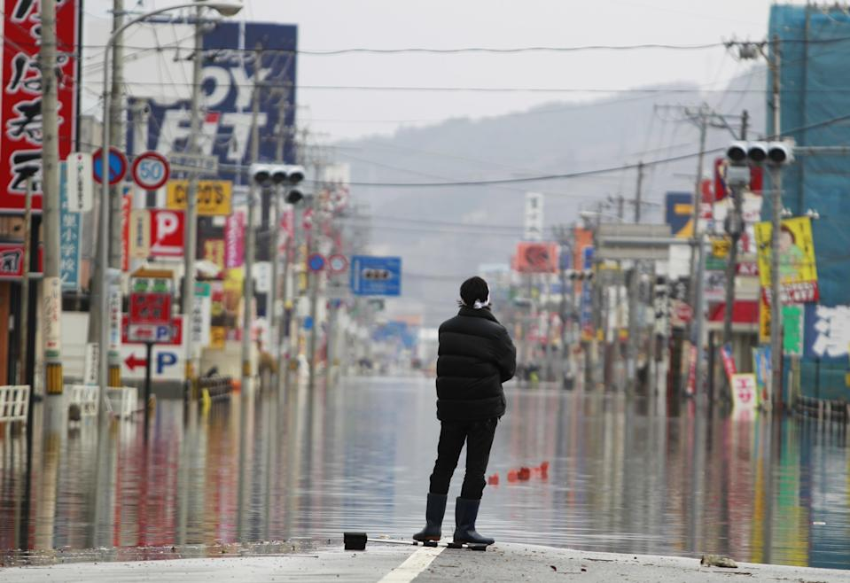 <p>FILE PHOTO: A man stands on the flooded street in the quake-hit area March 15, 2011 in Ishinomaki, Miyagi Prefecture, Japan. (Photo: XINHUA/Gamma-Rapho via Getty Images )</p>