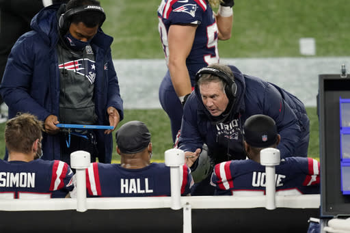 New England Patriots head coach Bill Belichick, right, coaches defenders John Simon, left, Terez Hall, center, and Josh Uche on the sideline during the first half of an NFL football game against the Buffalo Bills, Monday, Dec. 28, 2020, in Foxborough, Mass. (AP Photo/Elise Amendola)