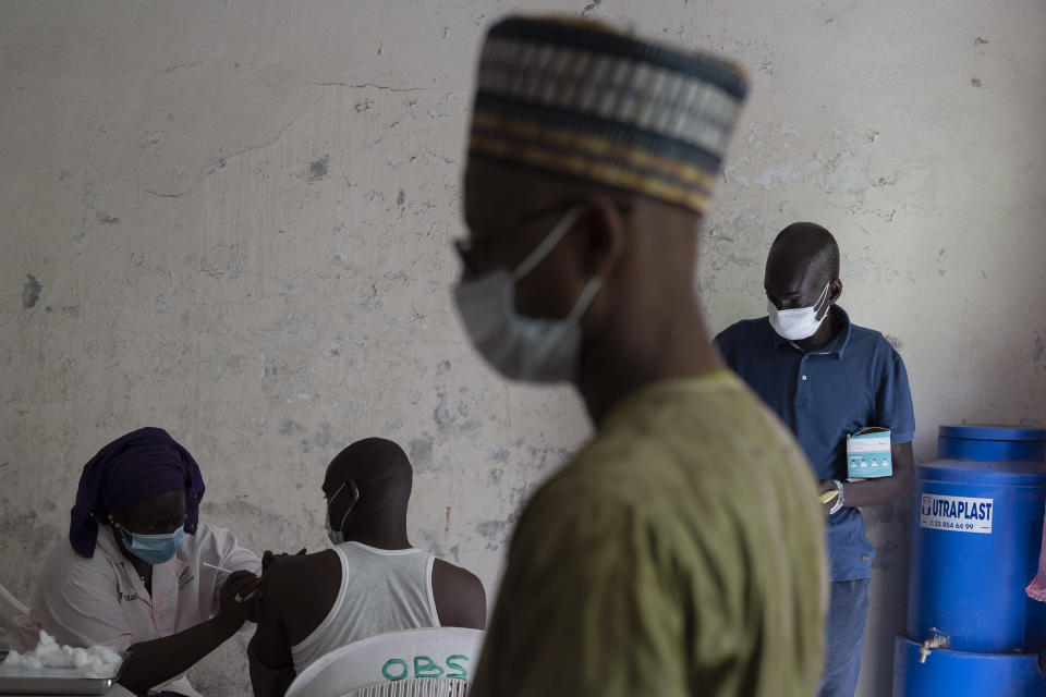 FILE—In this Wednesday, July 28, 2021 file photo, a health worker administers a dose of Janssen COVID-19 vaccine by Johnson & Johnson in the Medina neighborhood in Dakar, Senegal. Thousands of new coronavirus cases have been reported in West Africa in recent weeks amid low vaccination rates and the spread of the delta variant. Officials say cases have risen sharply in Senegal, Ghana, Nigeria and elsewhere. (AP Photo/Leo Correa, File)