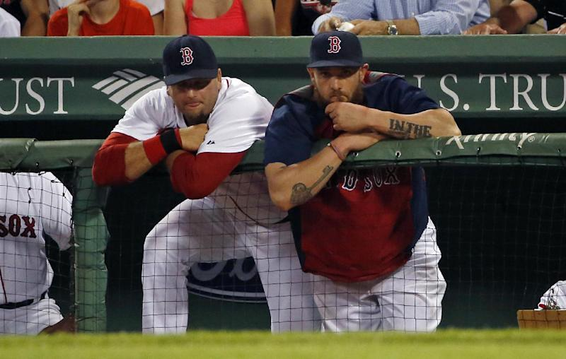 Boston Red Sox catcher A.J. Pierzynski, left, and left fielder Jonny Gomes watch from the dugout in the ninth inning of a baseball game against the Chicago White Sox at Fenway Park in Boston, Tuesday, July 8, 2014. The White Sox won 8-3. (AP Photo/Elise Amendola)
