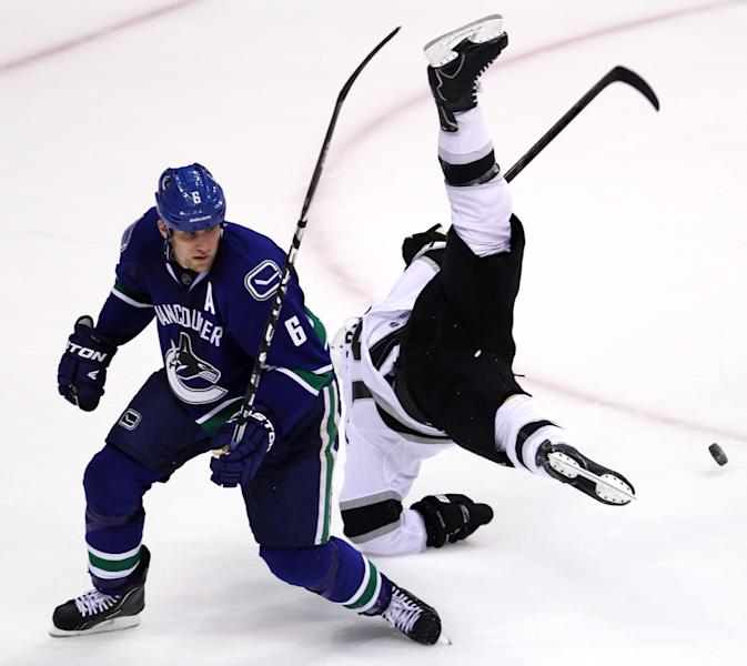 Los Angeles Kings center Mike Richards (10) flies through the air as he and Vancouver Canucks defenseman Sami Salo (6) fight for control of the puck during the second period of Game 2 of a first-round NHL hockey Stanley Cup playoff series in Vancouver, British Columbia, Friday, April, 13, 2012. (AP Photo/The Canadian Press, Jonathan Hayward)