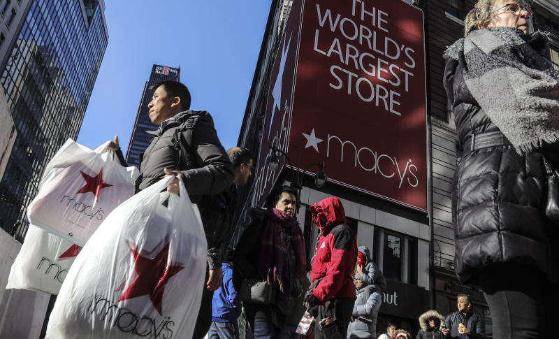 A shopper leaves Macy's department store with bags in both hands during Black Friday shopping, Friday Nov. 29, 2019, in New York. Black Friday shoppers fought for parking spots and traveled cross-state to their favorite malls, kicking off a shortened shopping season that intensified the mad scramble between Thanksgiving and Christmas. (AP Photo/Bebeto Matthews)