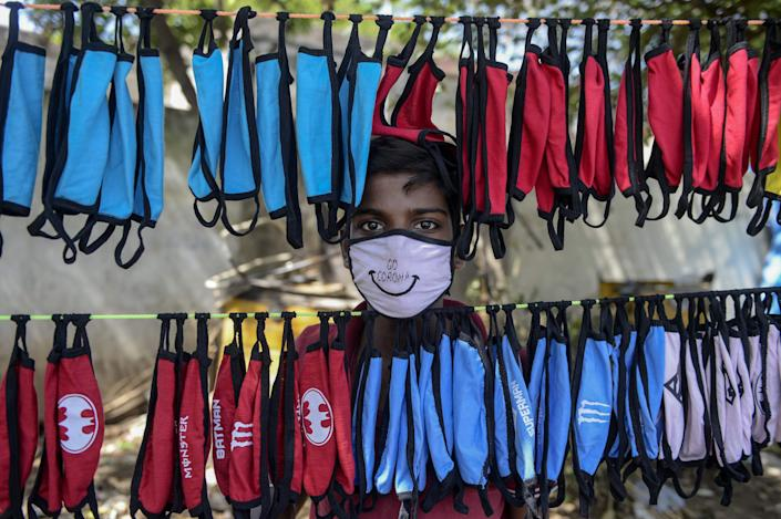 A street vendor poses as he arranges facemasks to sell on the roadside as a preventive measure against the spread of the COVID-19 coronavirus on the outskirts of Hyderabad, India on June 5, 2020.
