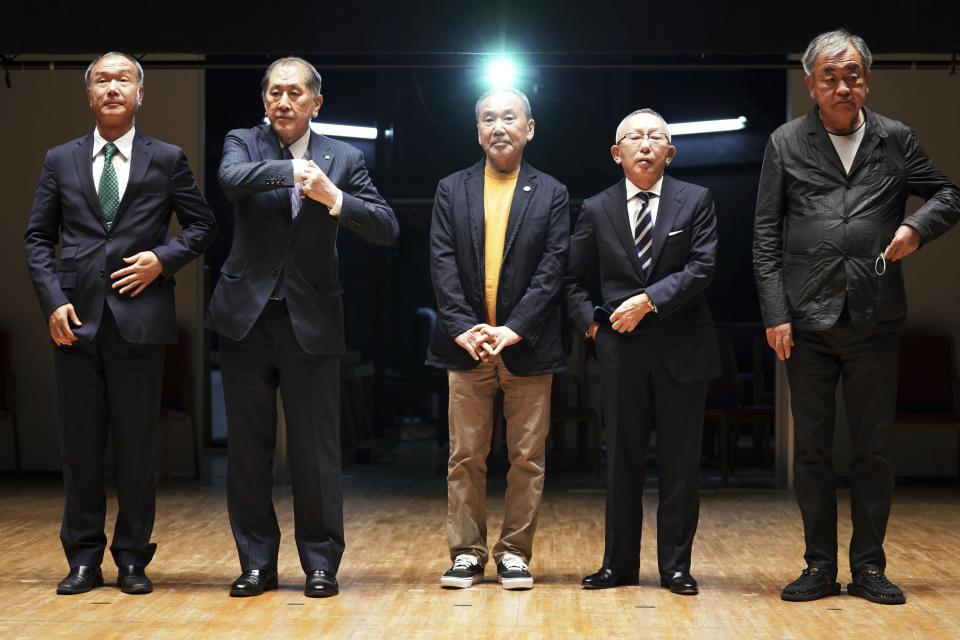"""Japanese novelist Haruki Murakami, center, Chairman, President and CEO, UNIQLO CO., LTD. Tadashi Yanai, second right, and Kengo Kuma, right, the architect behind the Olympic stadium, and other university officials pose for media during a press conference on the university's new international house of literature as known as The Haruki Murakami Library"""" at the Waseda University Wednesday, Sept. 22, 2021 in Tokyo. (AP Photo/Eugene Hoshiko)"""
