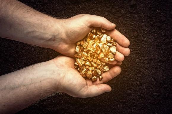 A man holding fragments of gold over soil.