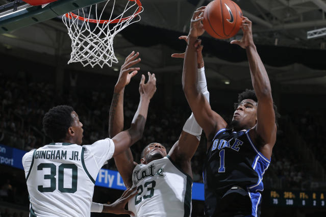 Duke's Vernon Carey Jr., right, and Michigan State's Xavier Tillman, center, and Marcus Bingham Jr., left, vie for a rebound during the first half of an NCAA college basketball game, Tuesday, Dec. 3, 2019, in East Lansing, Mich. (AP Photo/Al Goldis)