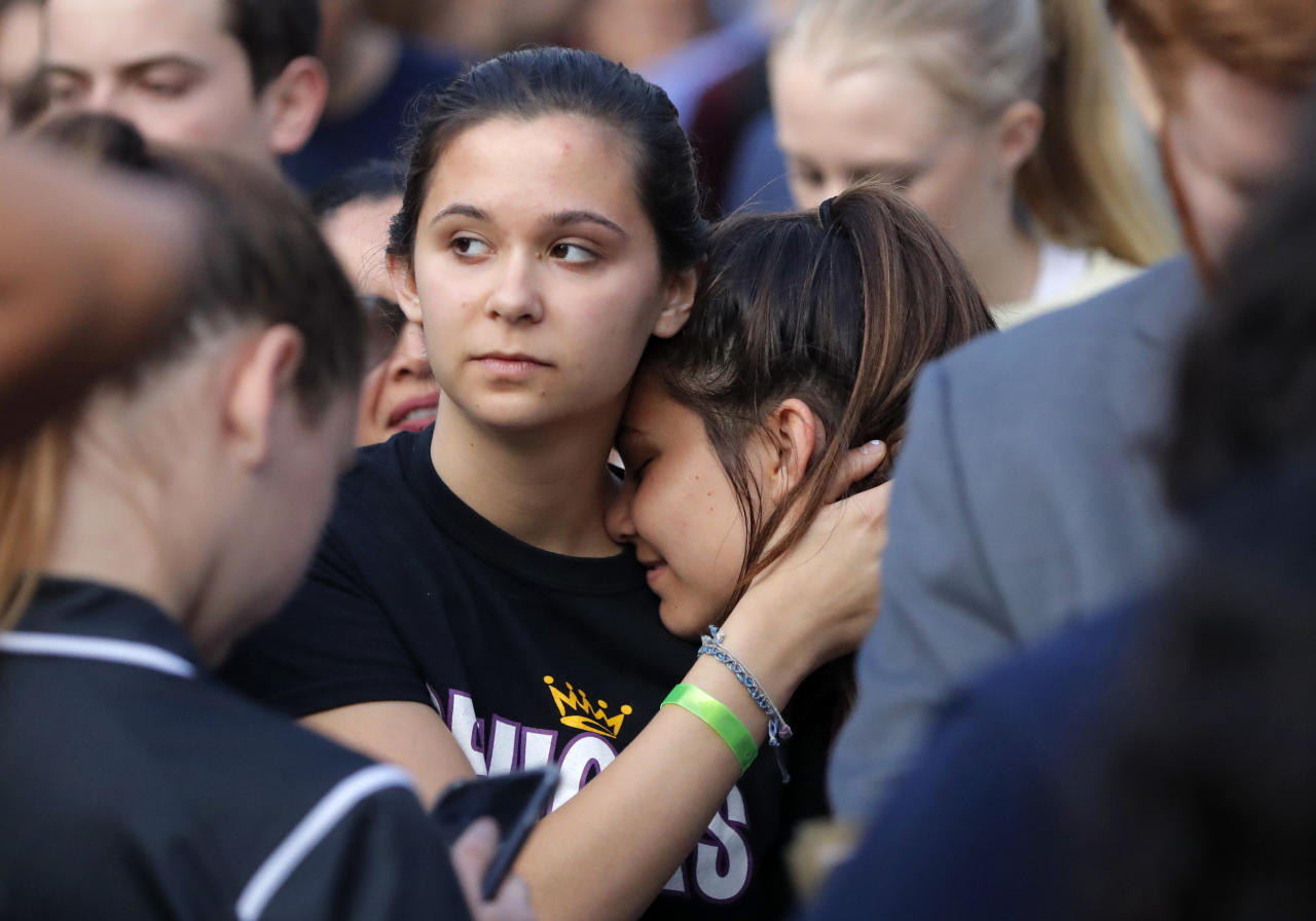 Julia Salomone, 18, left, and her sister Lindsey Salomone, 15, student survivors from Marjory Stoneman Douglas High School hug as they march to the state capitol to challenge lawmakers on gun control reform, in Tallahassee, Fla., Wednesday, Feb. 21, 2018. The students split into several groups to talk with lawmakers and other state leaders about gun control, the legislative process, and mental health issues. (AP Photo/Gerald Herbert)