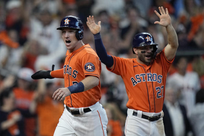 Houston Astros' Alex Bregman (2) and Jose Altuve (27) celebrate as they score on teammate Yuli Gurriel's single during the fifth inning in Game 2 of a baseball American League Division Series against the Chicago White Sox,Friday, Oct. 8, 2021, in Houston. (AP Photo/David J. Phillip)