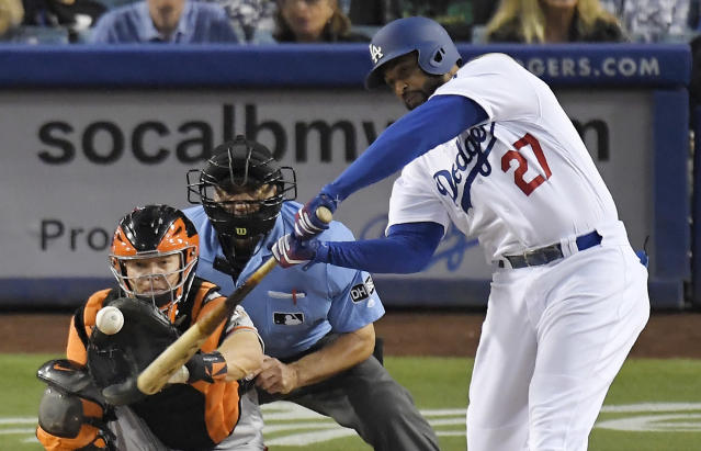 Los Angeles Dodgers' Matt Kemp, right, hits a solo home run as San Francisco Giants catcher Nick Hundley, left, watches along with home plate umpire Phil Cuzzi during the fourth inning of a baseball game Friday, June 15, 2018, in Los Angeles. (AP Photo/Mark J. Terrill)