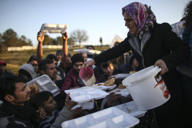 Migrants receive food as they gather in a field near Edirne. (AP)