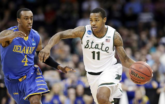 Michigan State's Keith Appling (11) drives in front of Delaware's Jarvis Threatt in the second half during the second round of the NCAA college basketball tournament in Spokane, Wash., Thursday, March 20, 2014. Michigan State won 93-78. (AP Photo/Elaine Thompson)