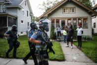 """FILE - In this May 28, 2020, file photo, protesters and residents watch as police in riot gear walk down a residential street, in St. Paul, Minn. Former Minneapolis police Officer Derek Chauvin faces decades in prison when he is sentenced Friday, June 25, 2021, following his murder and manslaughter convictions in the death of George Floyd. Floyd's death, filmed by a teenage bystander as Chauvin pinned Floyd to the pavement for about 9 and a half minutes and ignored Floyd's """"I can't breathe"""" cries until he eventually grew still, reignited a movement against racial injustice that swiftly spread around the world and continues to reverberate. (AP Photo/John Minchillo, File)"""