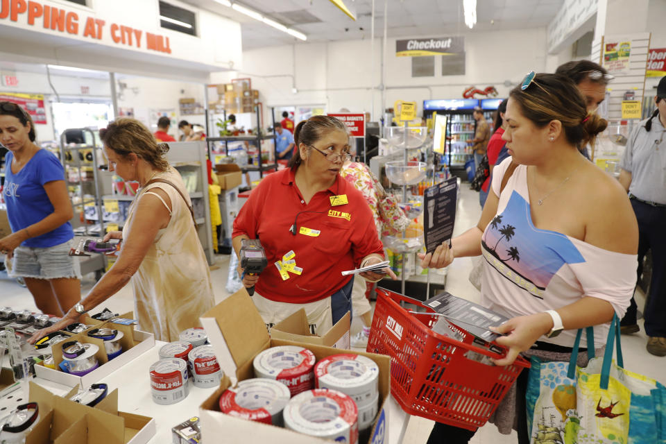 <p>City Mill hardware store sales associate Lisa Lavilla, left, talks to customer Ginger McCorriston about hurricane supplies, Wednesday, Aug. 22, 2018, in Honolulu. McCorriston was trying to find duck tape and batteries before they run out. (Photo: Marco Garcia/AP) </p>