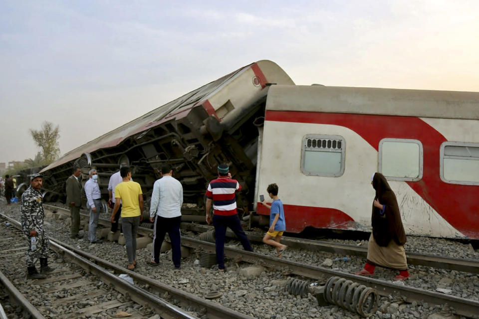 People gather at the site where a passenger train derailed injuring at least 100 people, near Banha, Qalyubia province, Egypt, Sunday, April 18, 2021. At least eight train wagons ran off the railway, the provincial governor's office said in a statement. (AP Photo/Fadel Dawood)