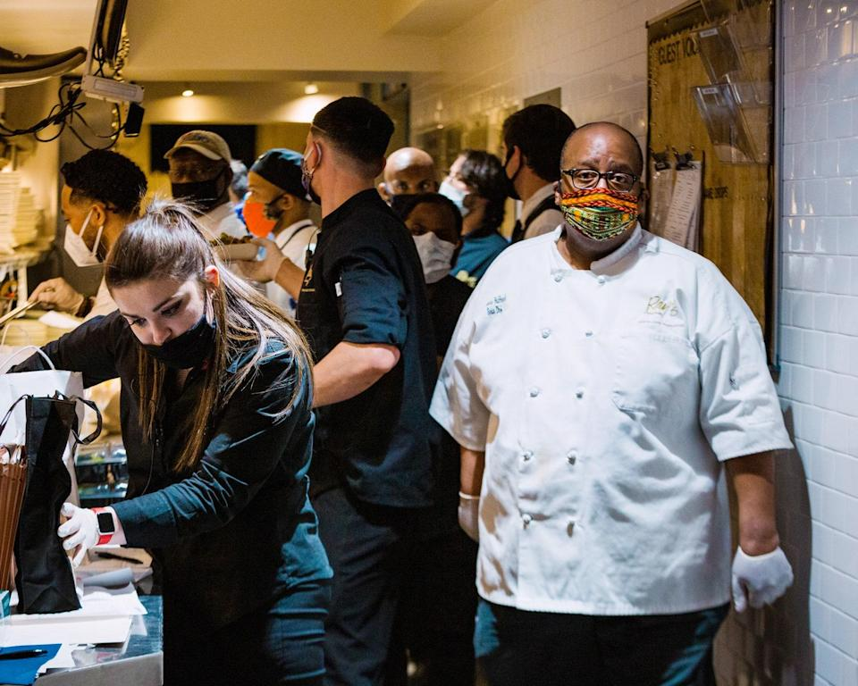 """<div class=""""caption""""> Sous chef Thomas Hubbard walks past a worker putting together a takeout order in the kitchen at Ray's On The River. </div> <cite class=""""credit"""">Dustin Chambers</cite>"""