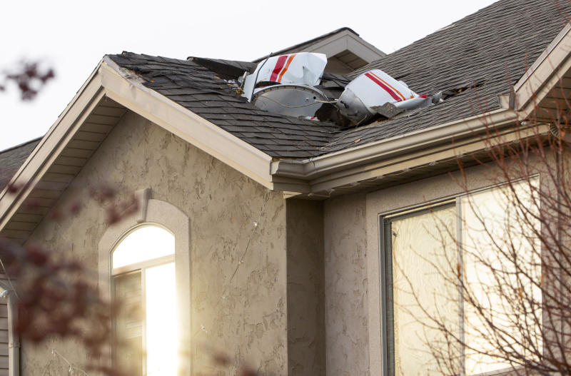 Debris from a small plane that crashed in Roy, Utah, is lodged in the roof of a home on Wednesday, Jan. 15, 2020. Authorities say the small plane crashed in a Utah neighborhood, killing the pilot as the aircraft narrowly avoided hitting any townhomes. Roy police Sgt. Matthew Gwynn said the 64-year-old pilot was making a short flight from Bountiful to Ogden in a twin-engine Cessna Wednesday but crashed in the city of Roy about 30 miles north of Salt Lake City. (Steve Griffin/The Deseret News via AP)
