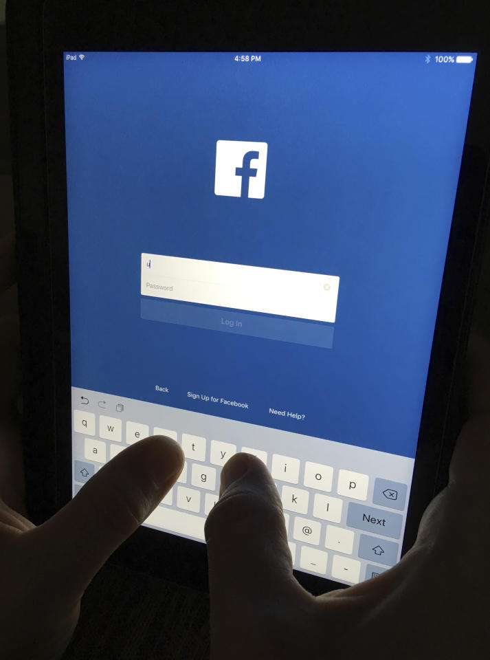 In this Monday, June 19, 2017, photo, a user signs into Facebook on an iPad, in North Andover, Mass. Facebook has squeezed just about as many ads into its main platform as it can. Any more and users might start to complain. Now, ads are moving on to Messenger, and WhatsApp may not be too far behind. (AP Photo/Elise Amendola)
