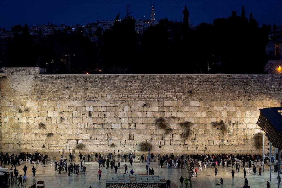 """<a href=""""https://www.cntraveler.com/story/in-tel-aviv-a-city-wide-socially-distanced-shabbat?mbid=synd_yahoo_rss"""" rel=""""nofollow noopener"""" target=""""_blank"""" data-ylk=""""slk:Israel"""" class=""""link rapid-noclick-resp"""">Israel</a> is acknowledged as the Holy Land in Judaism, Islam, and Christianity, and Jerusalem's Western Wall is its holiest site. The limestone structure has been a place of worship since the 11th century, as the closest place to Temple Mount (where it's said God created man) from which worshippers can pray. It's common practice for visitors to write their prayers, hopes, and wishes on slips of paper, then slide them into the cracks of the walls. The memos are collected throughout the year, before being buried in a Jewish cemetery on the nearby Mount of Olives."""