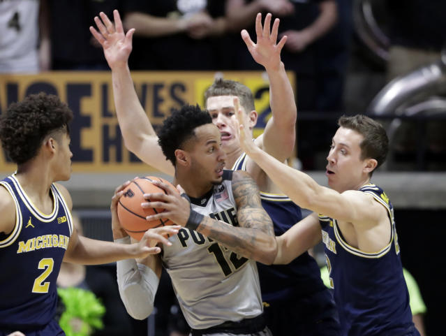 "Purdue forward <a class=""link rapid-noclick-resp"" href=""/ncaaf/players/260485/"" data-ylk=""slk:Vincent Edwards"">Vincent Edwards</a> (12) is stopped by Michigan guard <a class=""link rapid-noclick-resp"" href=""/ncaab/players/129025/"" data-ylk=""slk:Duncan Robinson"">Duncan Robinson</a> (22) and forward <a class=""link rapid-noclick-resp"" href=""/ncaab/players/131251/"" data-ylk=""slk:Moritz Wagner"">Moritz Wagner</a> (13) during the first half of an NCAA college basketball game in West Lafayette, Ind., Thursday, Jan. 25, 2018. (AP Photo/Michael Conroy)"
