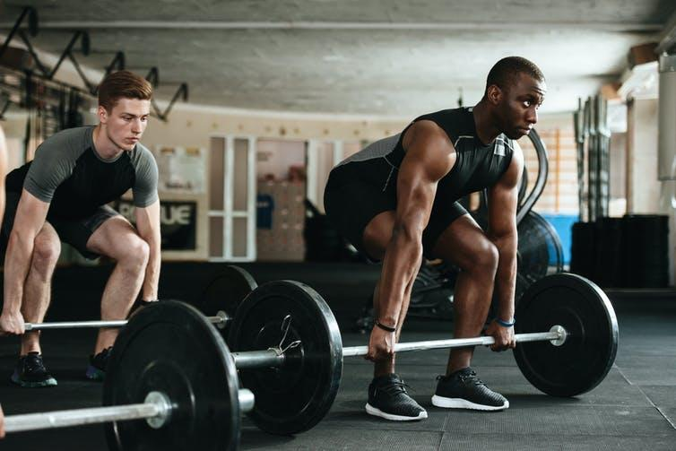 Two men lifting barbell with weights.