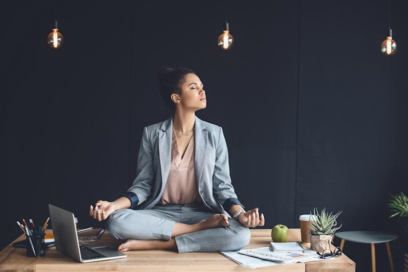 A young woman meditates on her desk at work.