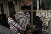Karla Perez and Esperanza Gonzalez warm up by a barbecue grill during power outage caused by the winter storm on February 16, 2021 in Houston, Texas