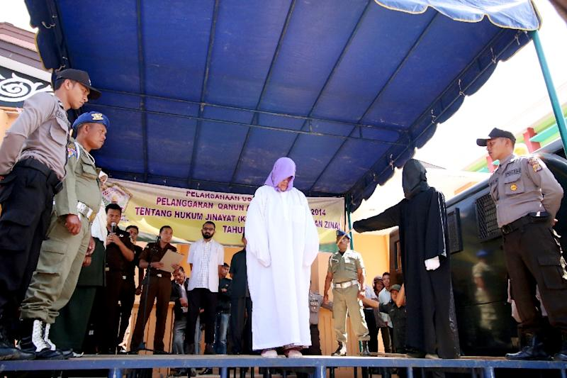 Sharia law enforcement officials cane a non-Muslim woman for selling alcohol in Takengon, in Aceh province, the first time someone from outside the Islamic faith has been punished there under strict religious laws (AFP Photo/)
