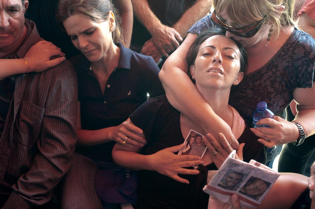 Relatives mourn Maor Harush who was killed in a suicide bombing in Bulgaria during his funeral in Acco, Israel, Friday, July 20, 2012. Israeli and American officials are blaming the Lebanese militant group Hezbollah for the bombing that killed five Israeli tourists, a Bulgarian bus driver and the bomber in the Black Sea resort town of Burgas, a popular destination for Israeli tourists. (AP Photo/Ahikam Seri)