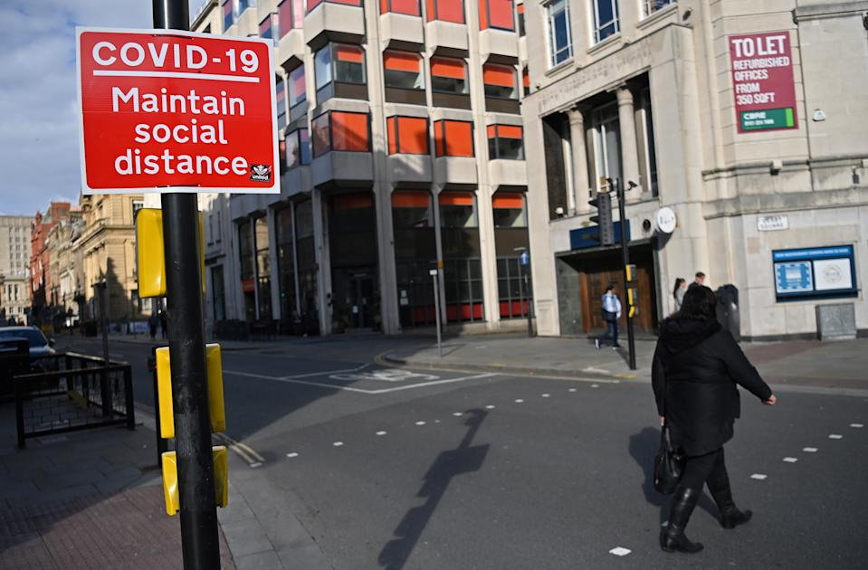 A pedestrian passes a Social Distancing sign as they cross an empty road in Liverpool, north west England on October 14, 2020, as new local lockdown measures come in to force to help stem a second wave of the novel coronavirus COVID-19. - The northwest English city of Liverpool was the first to be put in the government's new the highest risk category, with a ban on household mixing and pub closures coming into force Wednesday for at least four weeks. (Photo by Paul ELLIS / AFP) (Photo by PAUL ELLIS/AFP via Getty Images)