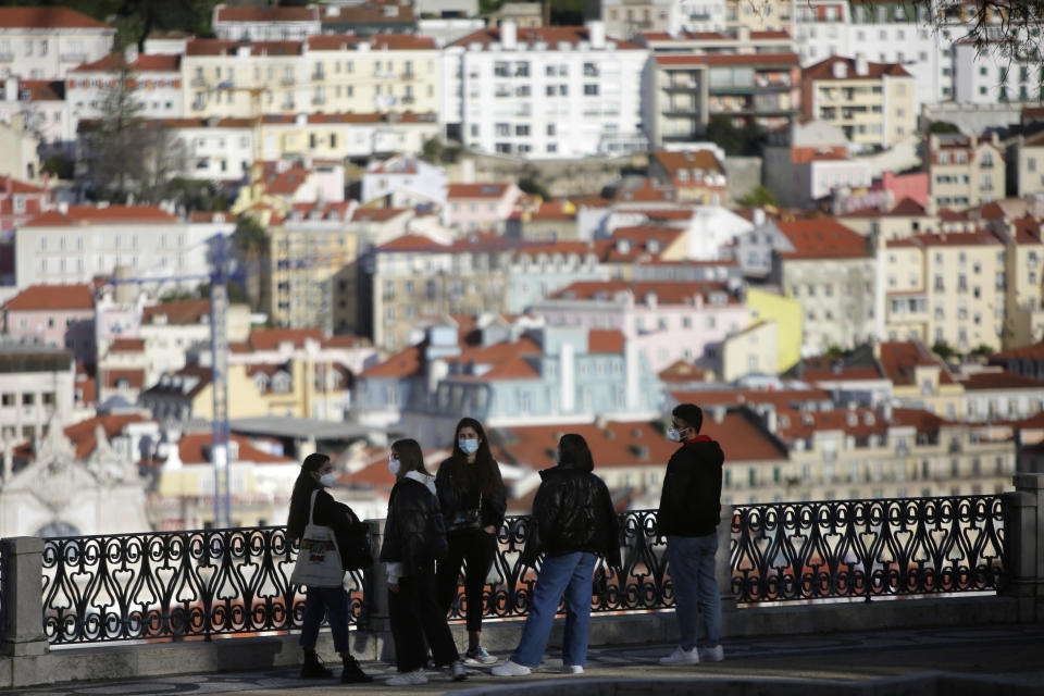 FILE - In this March 11, 2021 file photo, a group of young people wearing face masks chat at a viewpoint overlooking Lisbon's old center. Travel in and out of the Lisbon metropolitan area is to be banned over coming weekends as Portuguese authorities respond to a spike in new COVID-19 cases in the region around the capital, officials announced Thursday, June 17. (AP Photo/Armando Franca)