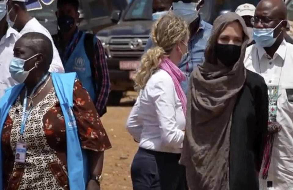In this image taken from video, Special Envoy to the United Nations High Commissioner for Refugees Angelie Jolie, right, visits the Malian refugee camp in Goudebo, Burkina Faso, Sunday June 20, 2021, to mark World Refugee day on Sunday. Hollywood actress Angelina Jolie has visited war-weakened Burkina Faso to show solidarity with people who continue to welcome the displaced, despite grappling with their own insecurity, and said the world isn't doing enough to help. (AP Photo)