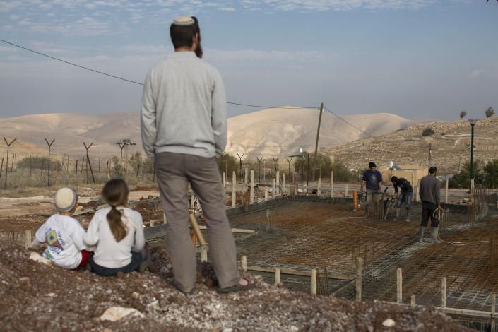 Jewish settler family members look at a construction of a new house at Gitit settlement in the West Bank's Jordan Valley, Thursday, Jan. 2, 2014. A senior Israeli Cabinet minister and more than a dozen hawkish legislators poured cement at a construction site in a settlement in the West Bank's Jordan Valley on Thursday, in what they said was a message to visiting U.S. Secretary of State John Kerry that Israel will never relinquish the strategic area. (AP Photo/Oded Balilty)