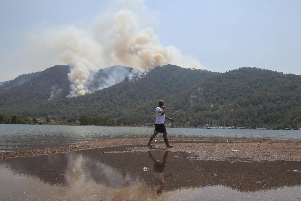 A man walks on the beach with a wildfire burning the forest in Turgut village, near tourist resort of Marmaris, Mugla, Turkey, Wednesday, Aug. 4, 2021. As Turkish fire crews pressed ahead Tuesday with their weeklong battle against blazes tearing through forests and villages on the country's southern coast, President Recep Tayyip Erdogan's government faced increased criticism over its apparent poor response and inadequate preparedness for large-scale wildfires.(AP Photo/Emre Tazegul)