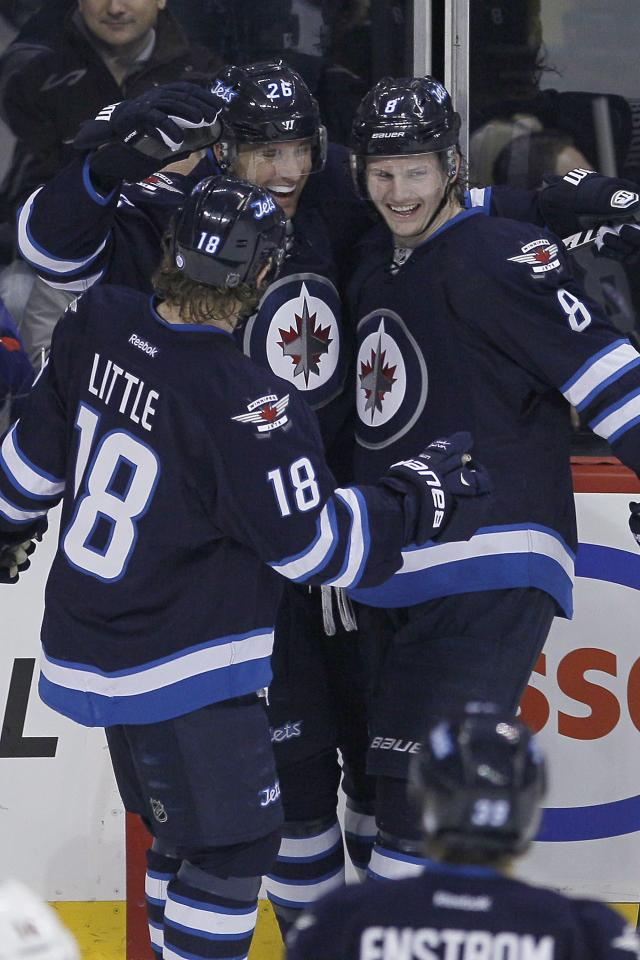 Winnipeg Jets' Bryan Little (18), Blake Wheeler (26) and Jacob Trouba (8) celebrate Wheeler's goal against the Minnesota Wild during first-period NHL hockey game action in Winnipeg, Manitoba, Friday, Dec. 27, 2013. (AP Photo/The Canadian Press, John Woods)