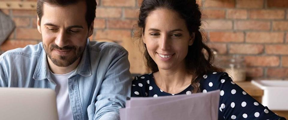 Happy young married couple reviewing loan, mortgage agreement, analyzing fee schedule, planning costs and family budget. Husband and wife using laptop and reading documents together