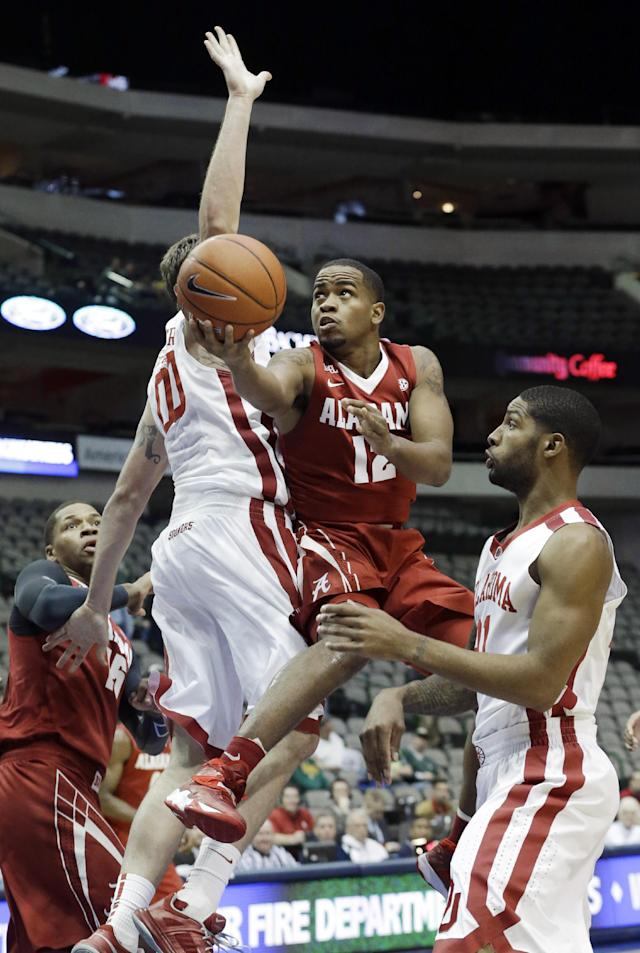 Alabama guard Trevor Releford (12) shoots between Oklahoma defenders Ryan Spangler (00) and Cameron Clark (21) during the first half of an NCAA college basketball game in Dallas, Friday, Nov. 8, 2013. (AP Photo/LM Otero)
