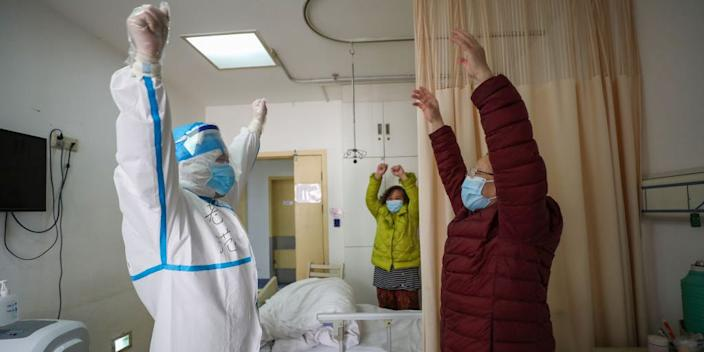 A respiratory specialist encourages a patient to exercise in a hospital in Wuhan, Hubei, on February 25, 2020.
