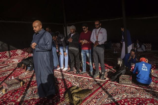 In this Monday, Jan. 13, 2020 photo, Muslims pray at a tent after stage eight of the Dakar Rally in Wadi Al Dawasir, Saudi Arabia. Formerly known as the Paris-Dakar Rally, the race was created by Thierry Sabine after he got lost in the Libyan desert in 1977. Until 2008, the rallies raced across Africa, but threats in Mauritania led organizers to cancel that year's event and move it to South America. It has now shifted to Saudi Arabia. The race started on Jan. 5 with 560 drivers and co-drivers, some on motorbikes, others in cars or in trucks. Only 41 are taking part in the Original category. (AP Photo/Bernat Armangue)