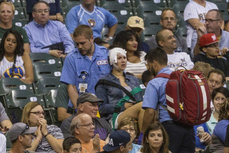 A woman, center, who was hit with a foul ball during a Milwaukee Brewers vs. Colorado Rockies game is carried out by medical staff in the second inning of the baseball game Tuesday, Aug. 23, 2016, in Milwaukee. (AP Photo/Tom Lynn)