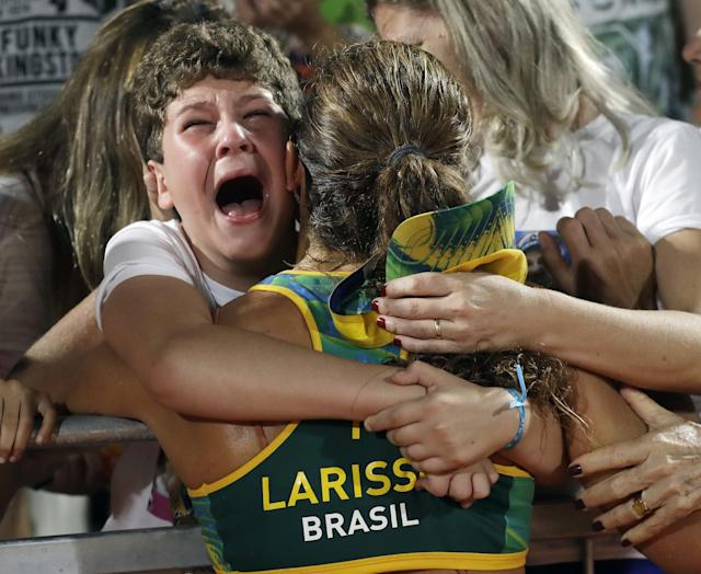 <p>Brazil's Larissa Franca, center, is hugged by loved ones after beating Switzerland during a women's beach volleyball quarterfinal match at the 2016 Summer Olympics in Rio de Janeiro, Brazil, Sunday, Aug. 14, 2016. (AP Photo/Marcio Jose Sanchez) </p>