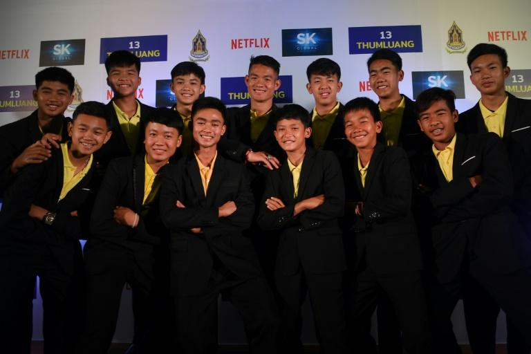 Members of the 'Wild Boars' football team pose for a photo with their coach Ekkapol Chantawong (back C) before a press conference in Bangkok on April 30, 2019 regarding a Netflix series about the rescue of the team from the Tham Luang cave. (AFP Photo/Lillian SUWANRUMPHA)